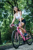 mujer joven, andar en bicicleta, en el parque foto