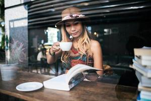 Woman drinking cappuccino and reading a book