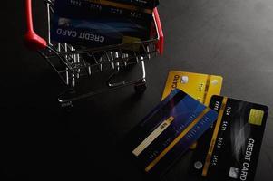Tarjetas de crédito en carrito de compras pequeño con espacio de copia foto