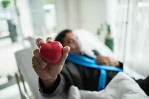 Hombre sujetando un corazón rojo en la mano en una cama de hospital