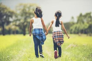 Two little girls holding hands in the park