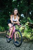 retrato de una mujer con una bicicleta rosa en el parque foto