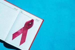Ribbon cancer sign on notebook photo