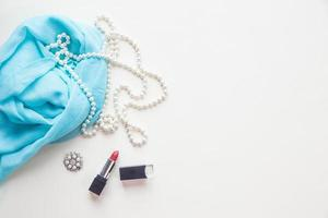 Vista superior de tela azul y perlas y lápiz labial.