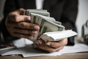 manos contando billetes de dólar foto
