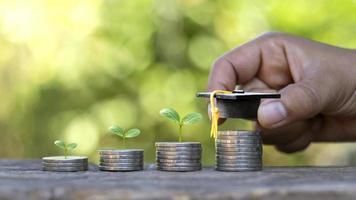sombreros de graduados en monedas y las manos de las personas, incluidos los árboles que crecen en la moneda. ideas de inversión para la educación