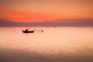 silueta de un barco en el agua al atardecer foto