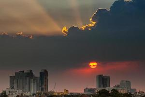 Orange and red sun and clouds over city