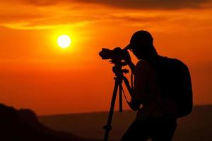 Silhouette of Asian person taking a photo in the sunset