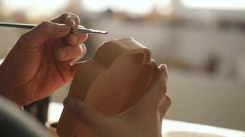 A Potter Applies Glaze with A Brush on A Clay Plate