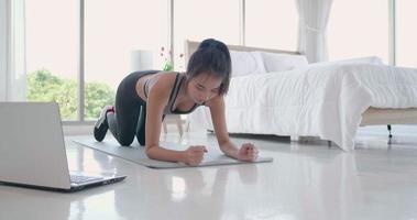 jovem fazendo prancha com um laptop para assistir a aula de ioga