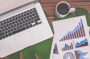 Business growth document, computer and coffee mug photo