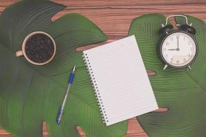 cuaderno, taza de café y despertador