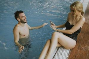Pareja joven relajándose en la piscina de la piscina interior foto