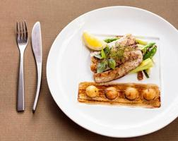 Fillet sea bass with vegetables and potatoes