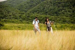 Pareja sonriente caminando con mochilas sobre colinas verdes foto