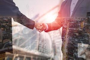 Double exposure of business people shaking hands photo