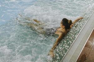 Mujer joven relajándose en la bañera de hidromasaje junto a la piscina foto
