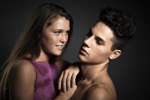 Retrato de una hermosa joven pareja feliz contra un fondo gris oscuro foto