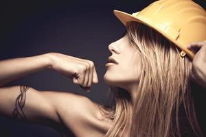 sexy, mujer joven, con, casco de seguridad, actuación, músculos foto