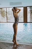 hermosa joven de pie junto a la piscina foto