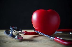 Estetoscopio y corazón rojo sobre fondo de madera foto