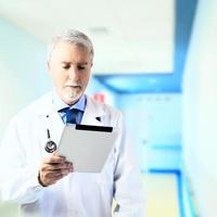 Doctor in the hospital hallway with a tablet photo