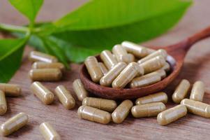 cápsulas de hierbas medicinales en carretes de madera foto
