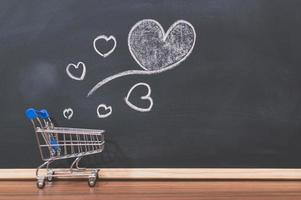 A small shopping cart and heart doodles on a blackboard