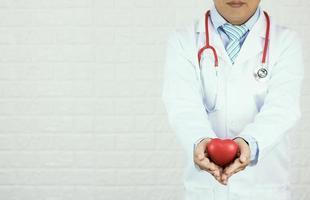 Doctor sosteniendo corazón rojo sobre fondo de pared de ladrillo blanco foto