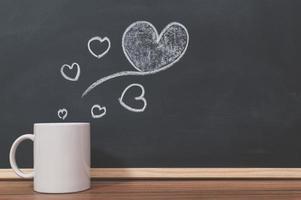 Coffee mug and heart doodle on the blackboard
