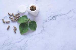 Medicina herbaria en cápsulas de mármol. foto