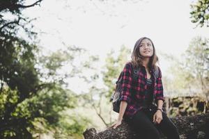 joven excursionista mujer sentada en la rama de un árbol