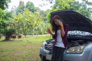 mujer joven con un coche averiado foto