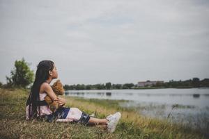 Niña sentada con su oso molesto en un campo de pradera foto