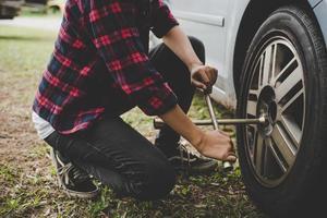 Mujer joven inconformista comprobando un pinchazo en su coche foto