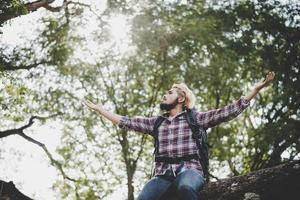 Joven excursionista hipster hombre sentado en la rama de un árbol con los brazos extendidos