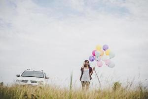 Beautiful young hipster woman holding colorful balloons outdoors photo
