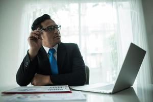 Young businessman working with laptop at office photo