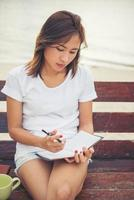 Young beautiful woman writing on notepad while sitting on bench photo