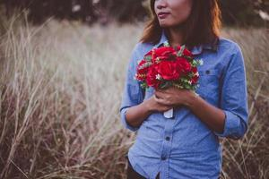 Young hipster woman in a field holding a bouquet of red roses