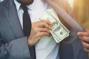Businessman placing money into his pocket photo