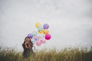 Hermosa joven inconformista sosteniendo globos de colores al aire libre foto