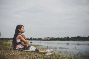niña sentada con su oso molesto foto
