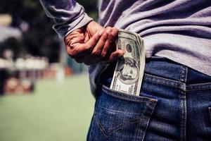 Man putting money in his pocket photo