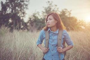 Vintage tone image of a beautiful young hipster woman with backpack in a meadow photo