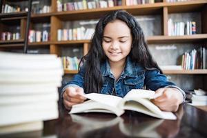 Mujer joven leyendo un libro sentado en el interior de un café urbano foto