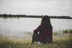 joven inconformista mujer sentada sobre la hierba cerca del lago relajante