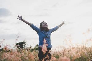 mujer joven feliz disfrutando de la puesta de sol foto