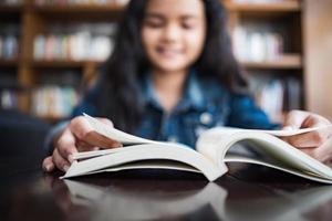 Mujer joven leyendo un libro sentado adentro en café urbano foto
